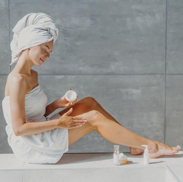 mujer aplicándose crema reductora en las piernas