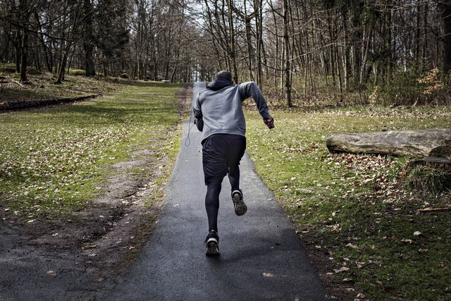 full length rear view of determined male athlete jogging on narrow street in forest