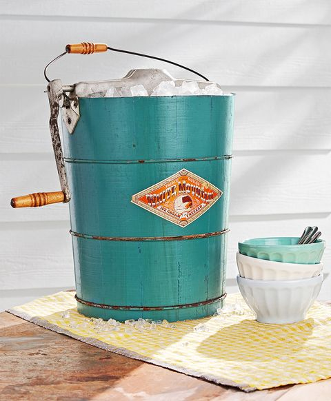 vintage teal-colored ice cream maker with stack of colorful bowls and spoons