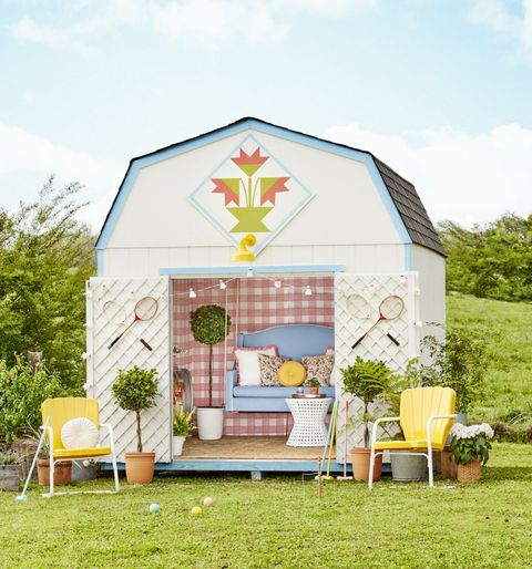 backyard shed decorated with wallpaper, a hanging swing, and outdoor furniture