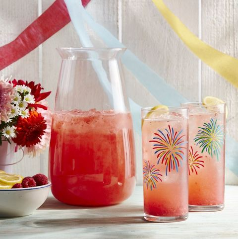 two glasses and a pitcher filled with pink raspberry lemonade