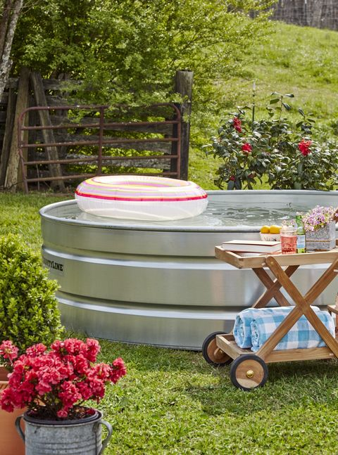 A stock tank pool in a yard with pool floatie and cart to the side with drinks and towels