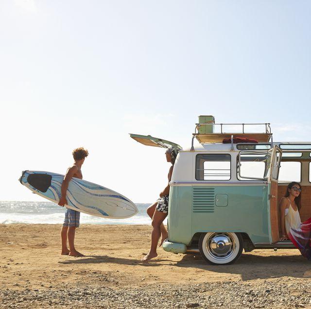 Furgoneta con surferos en la playa