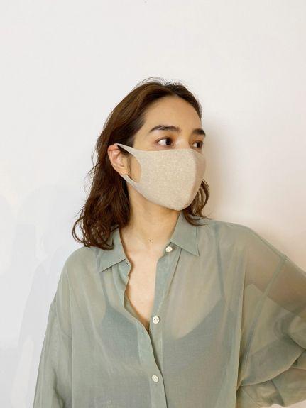 一個女生帶著米色口罩往左看