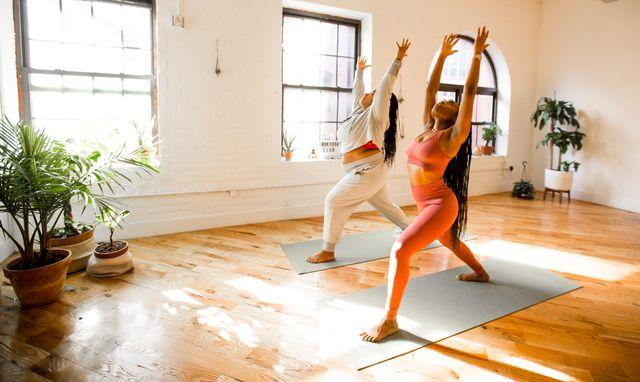 2 black women doing a yoga pose in a yoga studio