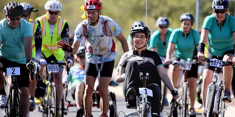 Former U.S. Rep. Gabrielle Giffords, front, rides in the El Tour de Tucson charity bike race on Saturday, Nov. 21, 2015, in Tucson, Ariz. Giffords was wounded in the 2011 shooting at a political event outside a Tucson grocery store where six people were k