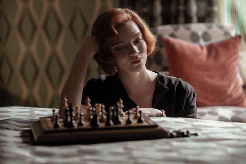 una chica mira el tablero de ajedrez