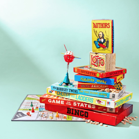 a stack of vintage board games including chutes and ladders and tiddledy winks