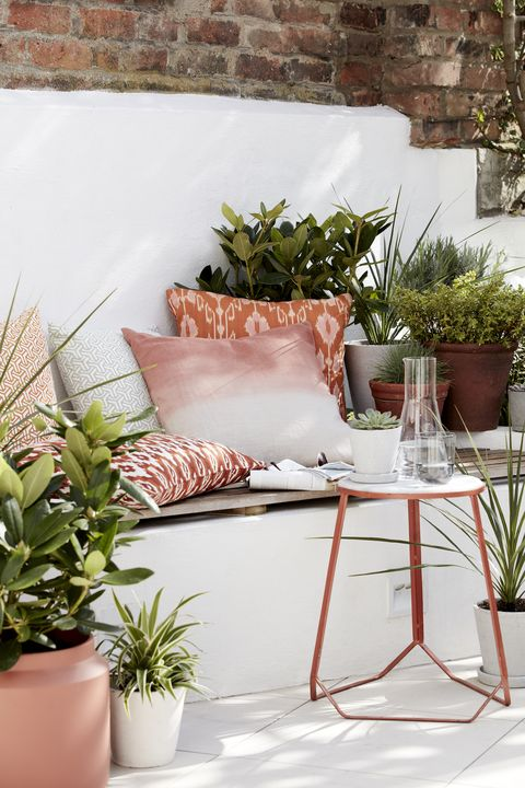 garden ideas, outdoor seating area filled with cushions, plants and a side table