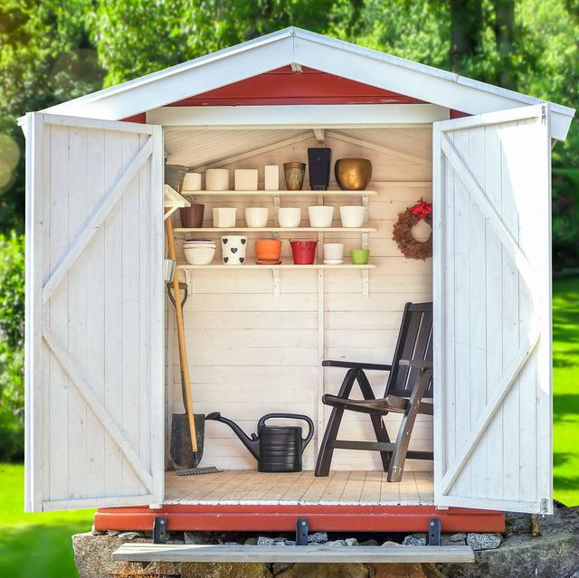 garden shed filled with gardening tools with green sunny garden in the background