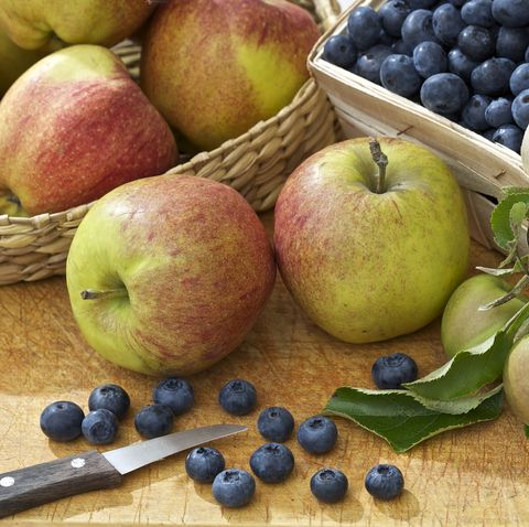 garden table with apples and basket of blueberries