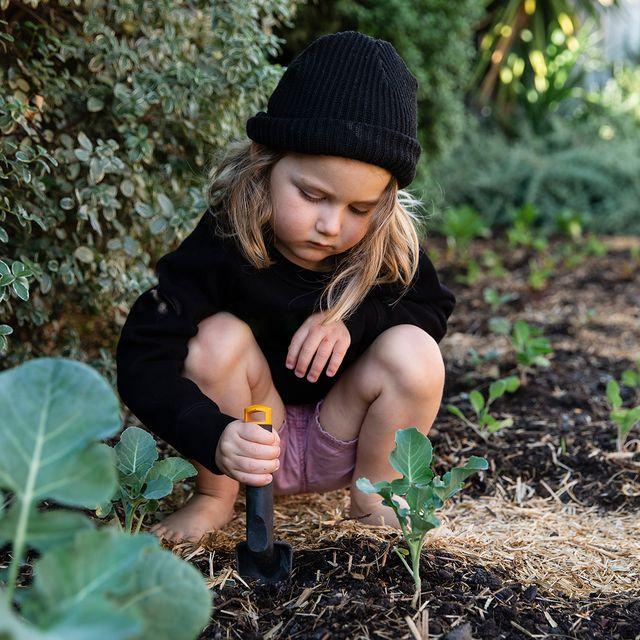 young kid digging in garden