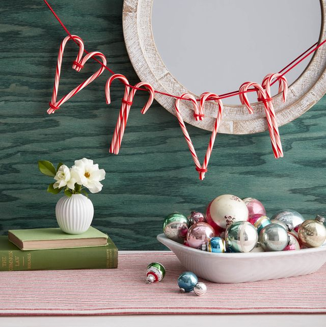 candy cane garland in front of a mirror on a green wall