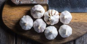 Garlic on wooden chopping board.