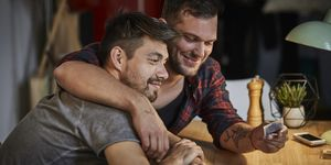 Gay couple hugging at table with playing cards