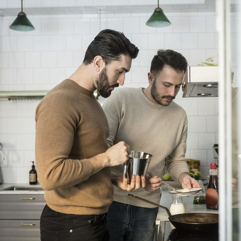 winter date ideas - Gay couple preparing food in kitchen at home
