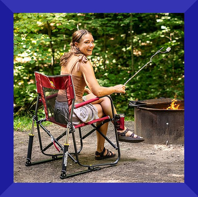 camper in gci outdoor portable rocking chair roasting smore by fire