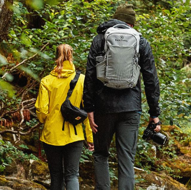 a man and woman walking in a forest