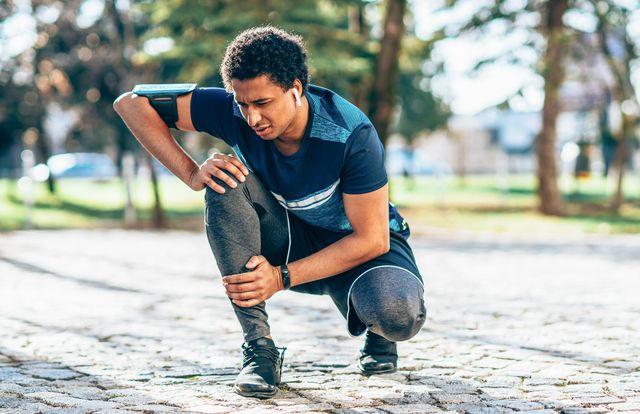 jonge man stopt met hardlopen en pakt scheen vast