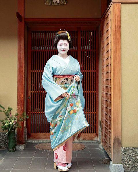 裾綿が入った二枚重ねの色紋付のお引きずり姿で、京舞井上流家元にご挨拶に。空色地に菊や藤などの花々が表された優美なきものに格調ある織り帯が美しく調和しています。1月3、7、15日の行事は黒紋付。14日までの他の日は色紋付を着ます。