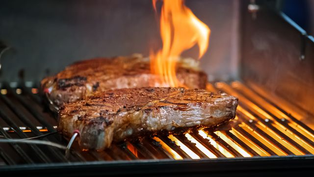steaks cooking on the grill