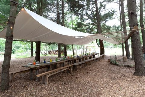 dining room with wooden tables and benches, under a tent with tarp-like material tied to trees lining the dining room