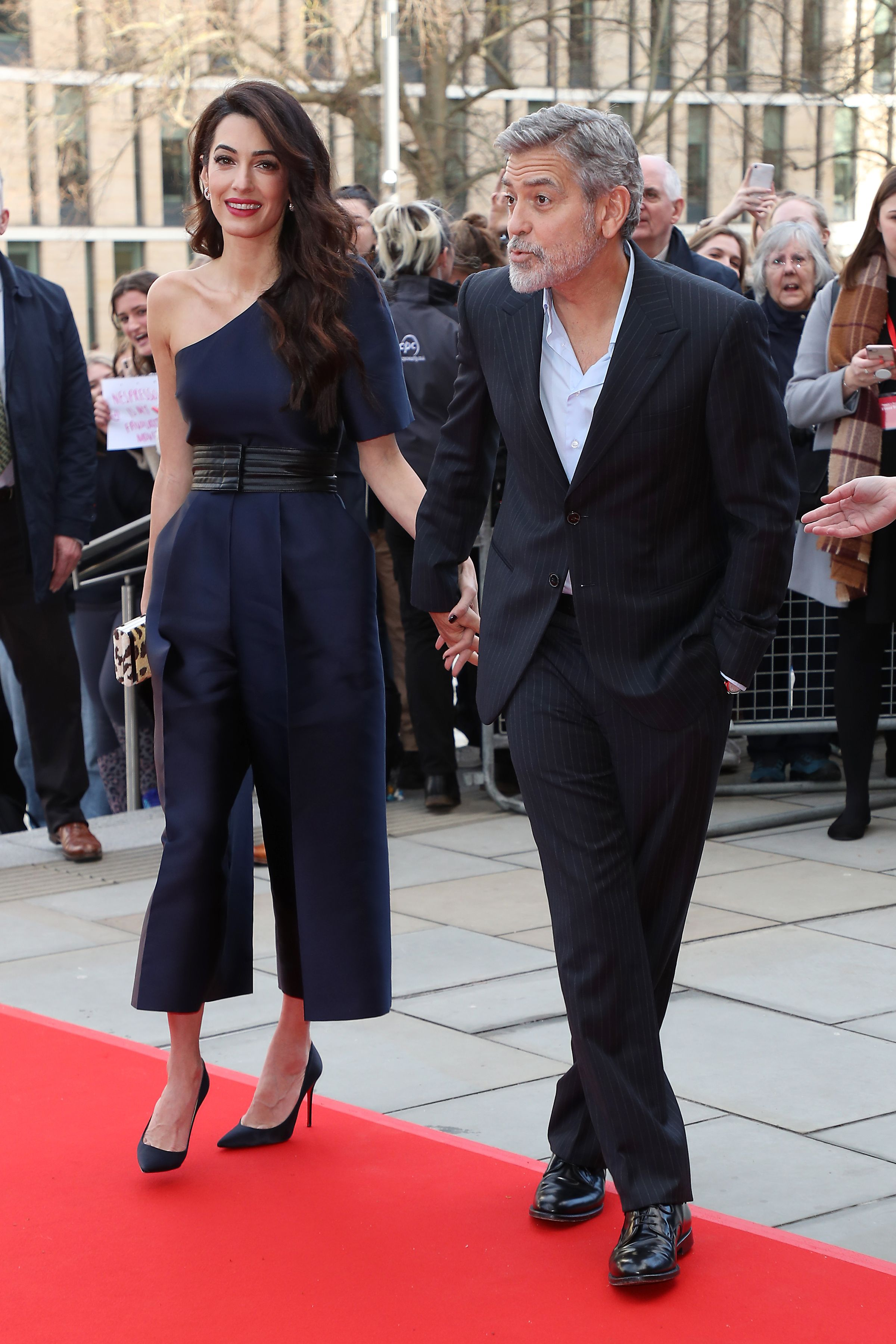 March 14, 2019 In a navy asymmetical jumpsuit with George Clooney at the People's Postcode Lottery Charity Gala at McEwan Hall in Edinburgh, Scotland.