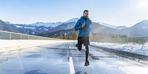 Germany, Bavaria, sportive man running on a road in winter