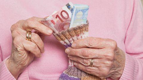 Oude vrouw haalt geld uit een sok