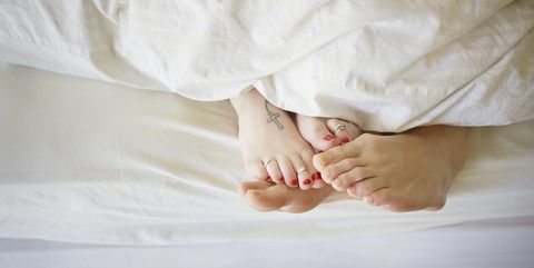 young couple in bed, feet touching