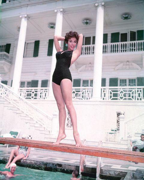 ریتا مورنو ، خواننده ، رقصنده و بازیگر پورتوریکویی ، با لباس شنای سیاه ، در هیئت غواصی در یک استخر شنا ، با شناگران در زیر ، در حدود سال 1955 عکس از مجموعه صفحه نقره ای گتی تصاویر