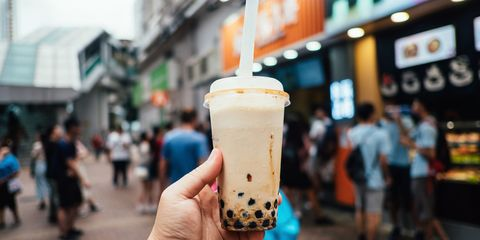 Human hand holding a bottle of iced cold bubble tea against city street in a hot summer day
