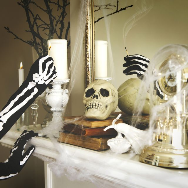 person dressed in a skeleton costume lights a candles halloween composition on fireplace