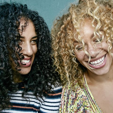 Portrait of two young women with long curly black and blond hair, smiling and laughing.