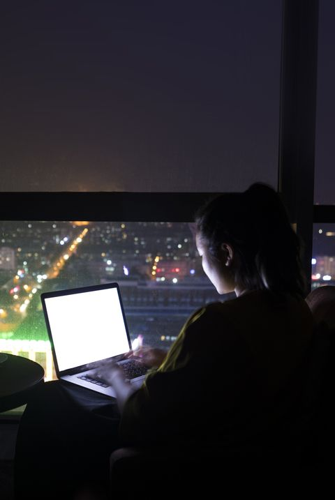 Woman using laptop at night by large windows