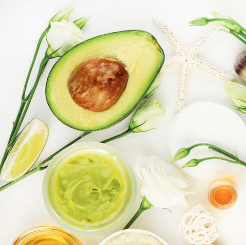 Avocado mask for beautiful skin and hair treatment. Facial mask in jar with essential oils and white blossom,