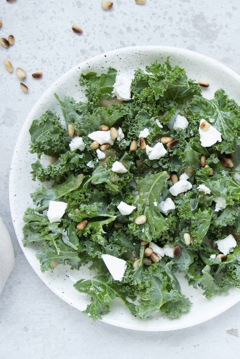 fresh kale salad with goat cheese, pine nuts and sweet balsamic vinegar dressing with onion on grey background