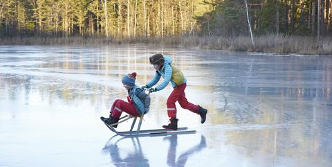 Boy pushing his brother on sleigh across frozen lake