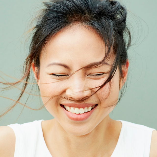 asian woman smiling with hair blowing in breeze