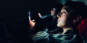 Women in bed in darkness using mobile phones