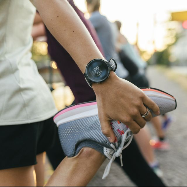 a close up of a woman stretching her legs before going on a run through the city