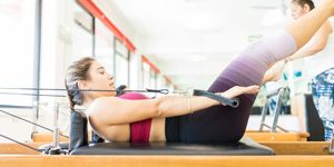 Female Exercising On Pilates Reformer In Health Club