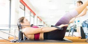 Female Exercising On Pilates Reformer In Health Club