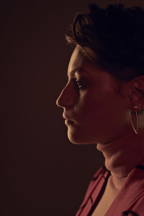Profile portrait of beautiful young woman looking away, shot on studio
