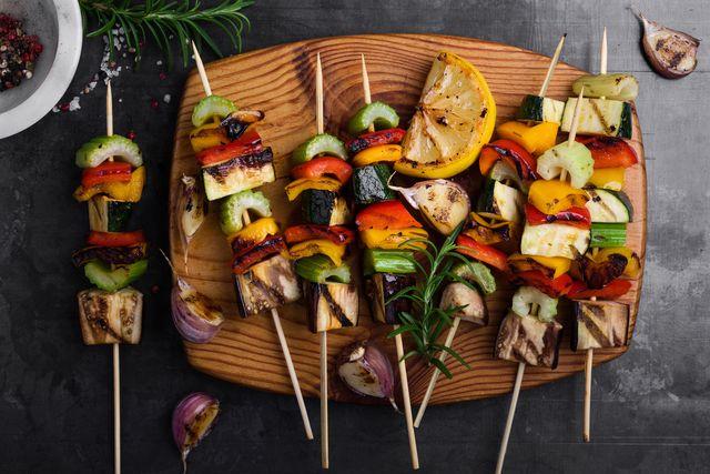 colorful grilled summer seasonal vegetables skewers on rustic wooden board viewed from above
