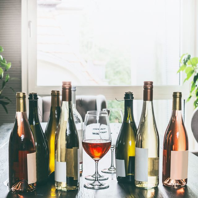 Variety of wine bottles and glasses on table in modern living room