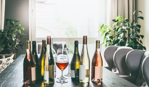 variety of wine bottles with mock up label and glasses on table in modern living room at window home party preparation
