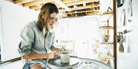 Woman spinning mug on potters wheel in garage studio