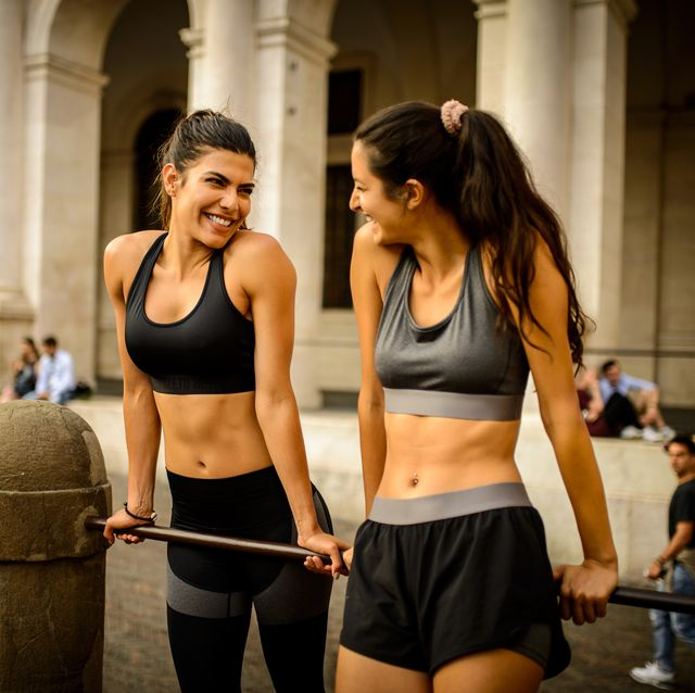 two sporty woman laughing after work out