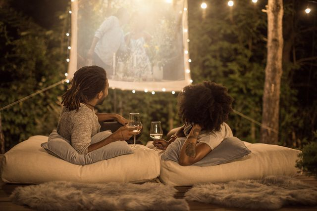 romantic couple sitting at backyard and looking movie at home improved theater backyard is decorated with string lights